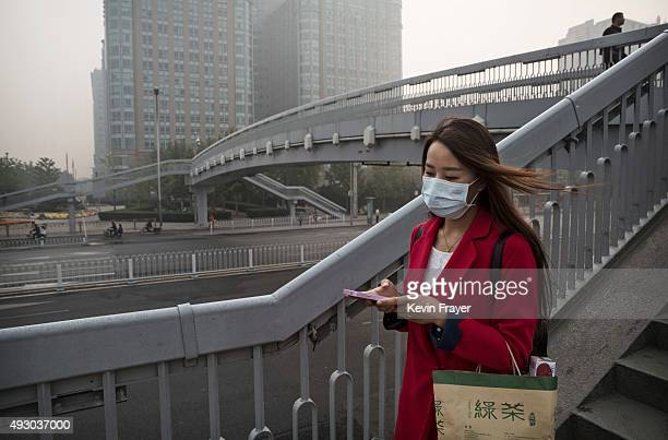 Chinese woman wears a mask as she crosses a footbridge during a polluted morning on October 17 2015 in Beijing China As a result of industry the use...
