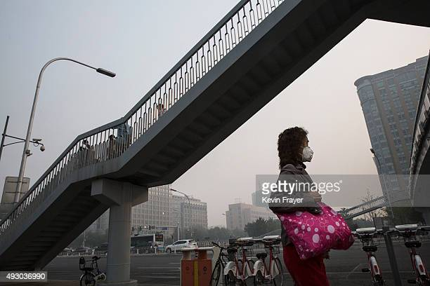 Chinese woman wears a mask during a polluted morning on October 17 2015 in Beijing China As a result of industry the use of coal and automobile...