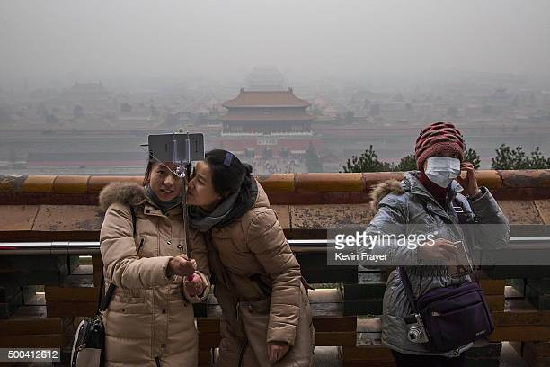 Chinese woman wears a mask to protect against pollution as two women take a picture together while visiting Jingshan Park overlooking the Forbidden...