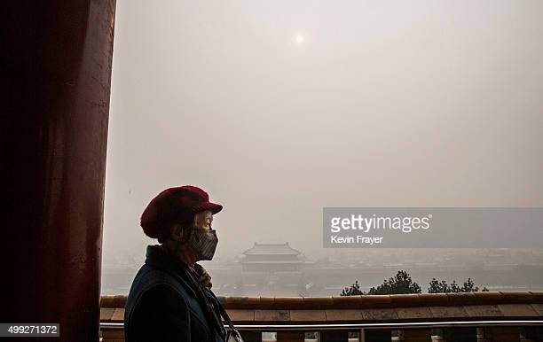 Chinese woman wears a protective mask as she overlooks the Forbidden City shrouded in haze on a day of heavy pollution on November 30 2015 in Beijing...