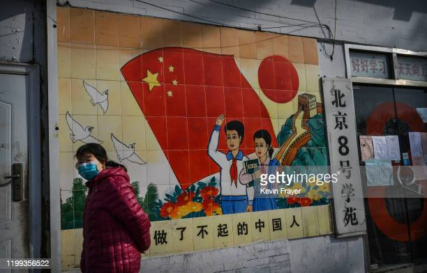 Chinese woman wears a protective mask as she passes a propaganda mural reading Be an extraordinary Chinese on February 8 2020 in Beijing China The...