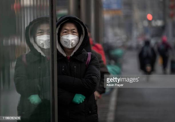 Chinese woman wears a protective mask as she waits for a bus on February 7 2020 in Beijing China The number of cases of a deadly new coronavirus rose...