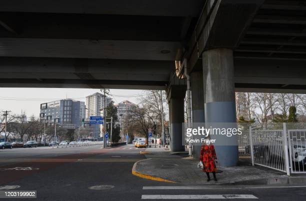 Chinese woman wears a protective mask as she waits to cross a nearly empty intersection on February 25 2020 in Beijing China The number of cases of...