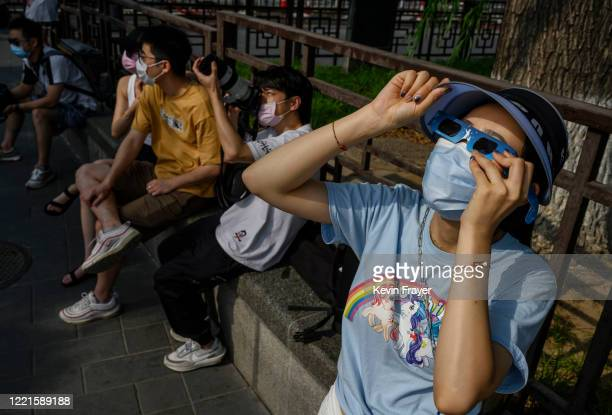Chinese woman wears a protective mask to prevent COVID-19 and protective glasses as she watches the sun during the annular solar eclipse outside the...