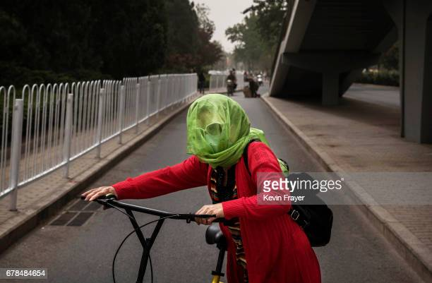 Chinese woman wears a scarf around her head to protect from particles blown in during a sandstorm as she gets on her bike on May 4 2017 in Beijing...
