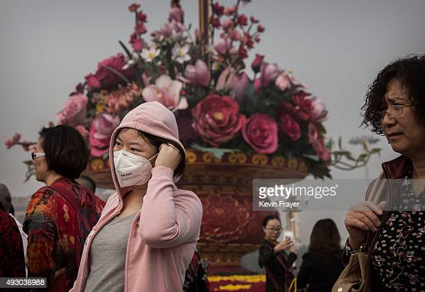 Chinese woman wears as mask as she and others stand near a flower arrangement in Tiananmen Square during a polluted morning on October 17 2015 in...