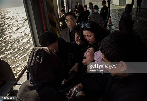 Chinese woman weeps as she reacts after placing the ashes of a relative in a metal chute during a sea burial organized by the Funeral and Internment...