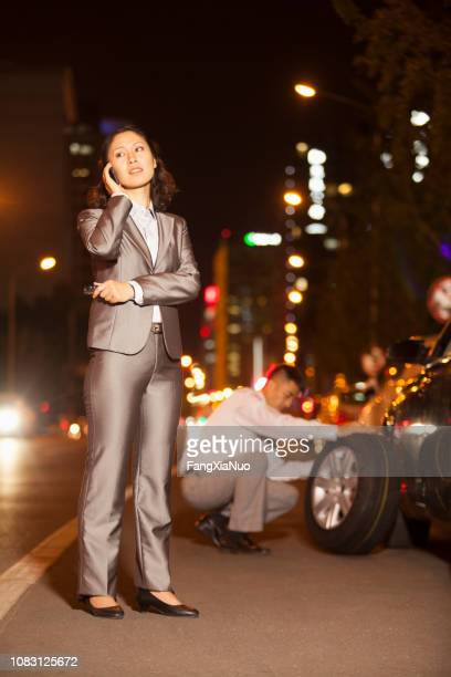chinese woman with colleague changing car tire - tow truck stock pictures, royalty-free photos & images