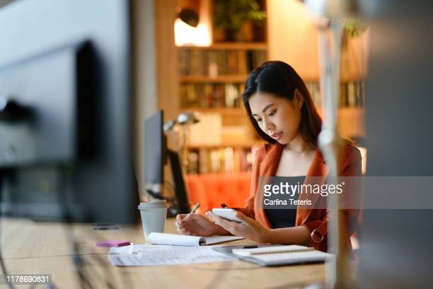 Chinese woman working late at night on business plans