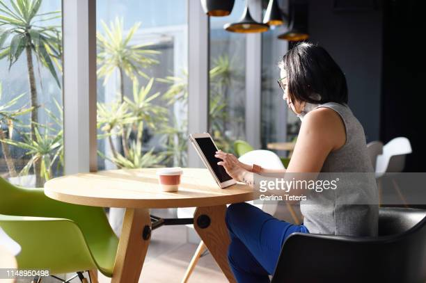 chinese woman working on a tablet at an office table - sustainable architecture stock pictures, royalty-free photos & images