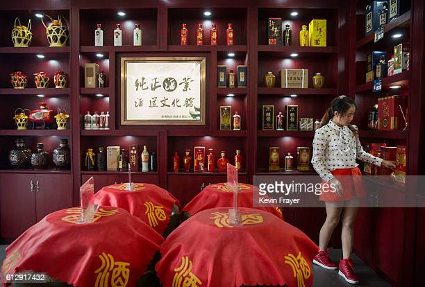 Chinese woman works in a shop selling locally made wine called baijiu on September 24 2016 in Maotai on the Chishui River in Guizhou province China...