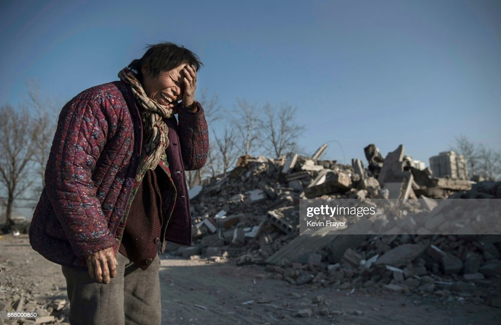 Chinese woman Zheng Yuzhi, 59, whose apartment was demolished by authorities three months ago and is now homeless, cries as she tells her story near buildings demolished by authorities in an area that used to have migrant housing on December 5, 2017 in the Changing District of Beijing, China. Thousands of migrant workers have been forcibly evicted in recent weeks in a sweeping government safety campaign following a deadly fire at a housing settlement. Many migrants, who came to Beijing from poor rural areas to find employment, say they were given little notice to leave and cannot afford to move somewhere else. The government's plan to demolish the buildings was actually announced in a 2015 strategy to reduce and cap the capital's population, but the mass evictions were accelerated after the fire and have stirred public backlash. The migrant population typically work in jobs such as construction, sanitation, and deliveries that have effectively built Beijing and keep it running. Some companies announced assistance and temporary housing for employees who have been affected, but many migrants say they have little choice but to move back to their hometowns.