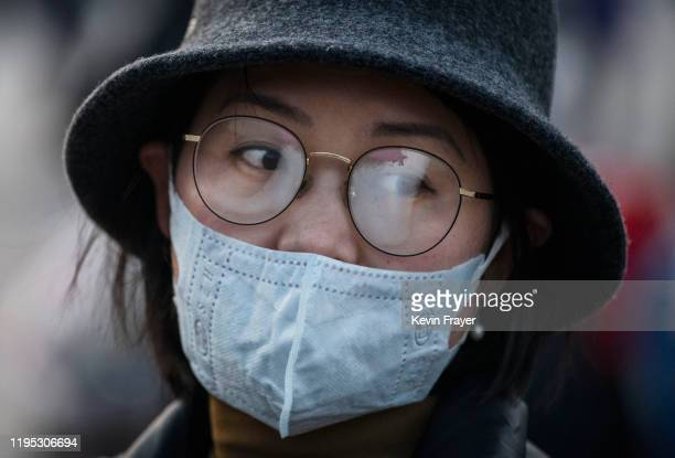 Chinese woman's glasses fog up while wearing a protective mask at Beijing Station before she boarded a train before the annual Spring Festival on...