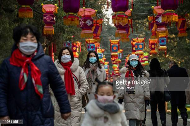 Chinese women and a child all wear protective masks as they walk under decorations in a park after celebrations for the Chinese New Year and Spring...