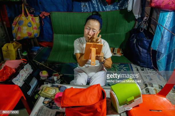 Chinese women applies her makeup before start a traditional Opera show as part of entertainment during The Nine Emperor Gods Festival inside the...