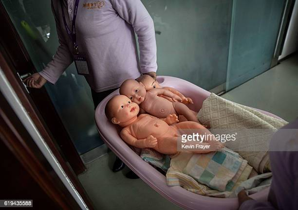 Chinese women carry plastic babies in a tub at a course to train to be qualified nannies known in China as ayis at the Ayi University on October 28...