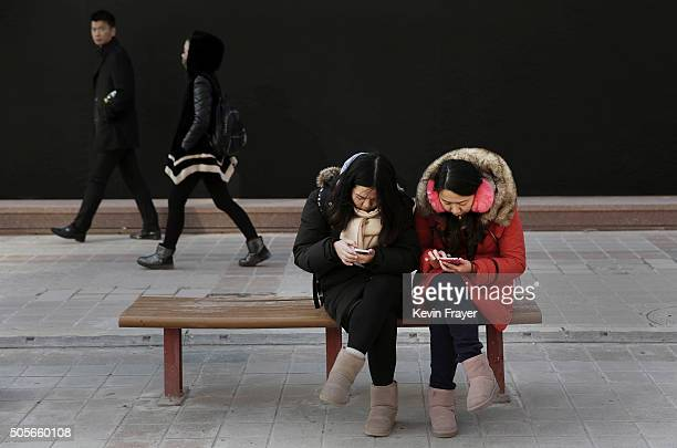 Chinese women check their mobile phones at a market on January 19 2016 in Beijing China In 2015 China's economy grew at its slowest rate in a quarter...