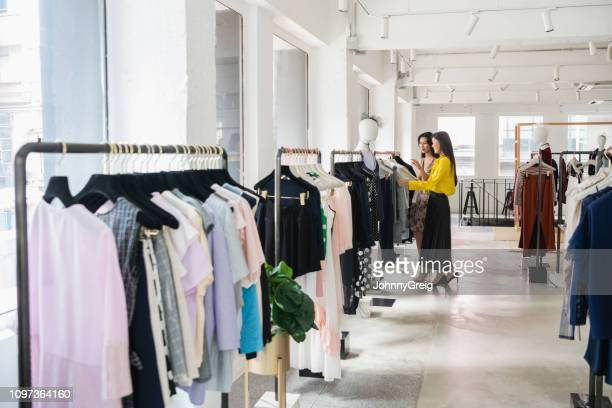chinese women choosing from clothes rail in shop - fashion hong kong stock photos and pictures