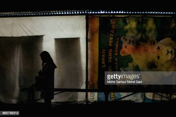 Chinese women is silhouetted as she waits for her turn to burn the joss paper as she performs a prayer during The Nine Emperor Gods Festival inside...