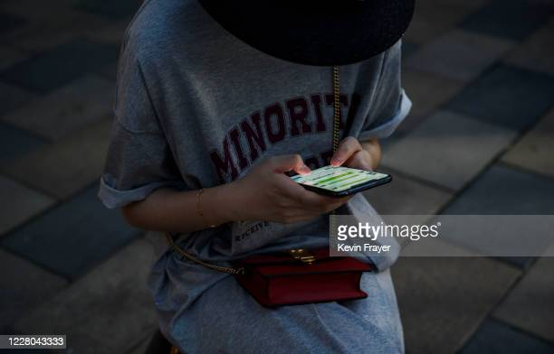 Chinese women looks at the messaging platform We Chat on her smartphone as she sits in a shopping area on August 14, 2020 in Beijing, China.