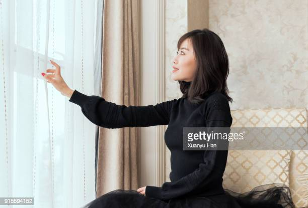 chinese women opening the curtain of a window - long sleeved stock photos and pictures