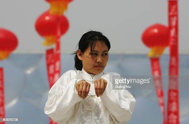 Chinese women perform traditional martial arts in front of the National Stadium, also known as the 'Bird's Nest' during a long-distance race on April...
