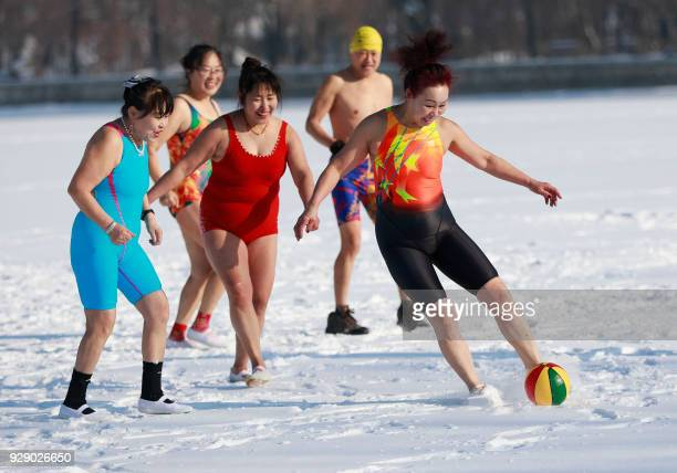 TOPSHOT Chinese women run with a ball on a snow covered field in Shenyang in China's northeastern Liaoning province during International Women's Day...