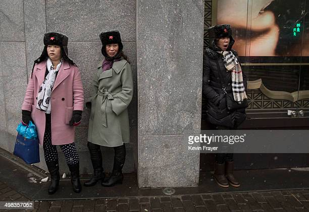 Chinese women stand out of the weather near the Forbidden City during a snowfall on November 22 2014 in Beijing China China's capital and other parts...