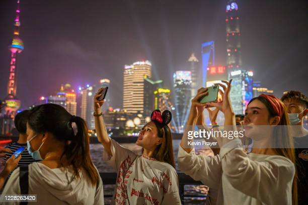 Chinese women take photos as they visit the Bund along the Huangpu River as the skyline of the city in the Pudong district is seen on August 29, 2020...