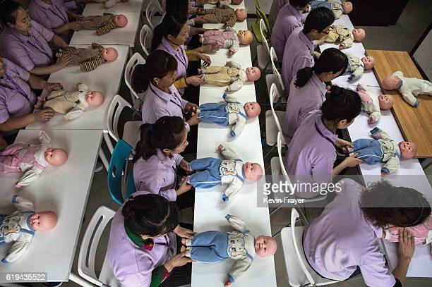 Chinese women training to be qualified nannies known in China as ayis learn techniqiues with plastic babies at the Ayi University on October 20 2016...