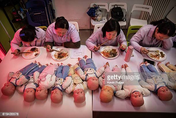 Chinese women training to be qualified nannies known in China as ayis eat their lunch next to plastic babies used for training during a break in...
