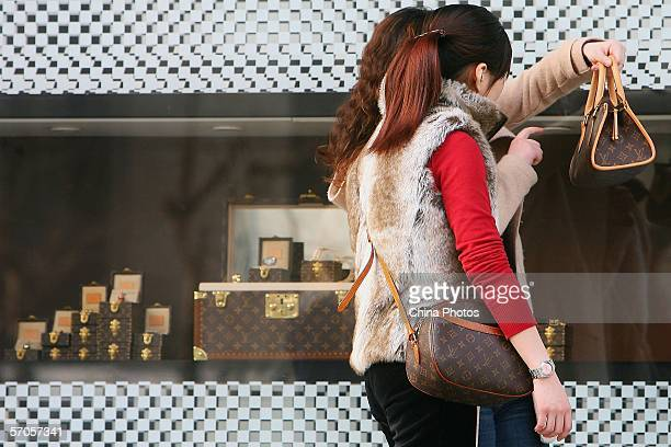 Chinese Women view the bags they bought at a Louis Vuitton flagship store on March 10, 2006 in Shanghai, China. According to state media, statistics...