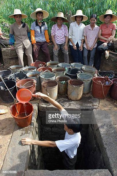 Chinese women wait as a man scoops water for them from a well on June 2 2005 in Leizhou of western Guangdong Province southern China According to...