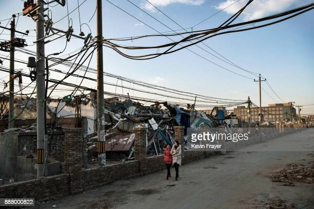 Chinese women walk by buildings demolished by authorities in an area that used to have migrant housing and factories on December 6 2017 in the Daxing...