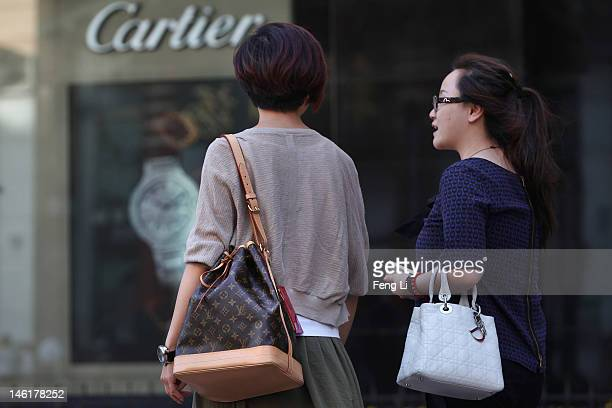 Chinese women walk past the Cartier store on June 11 2012 in Beijing China According to the World Luxury Association 2011 annual official report...