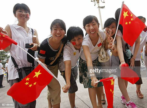 Chinese women wave their national flag as they attend the Olympic torch relay ceremony in Tiananmen Square in Beijing on August 6 2008 two days ahead...