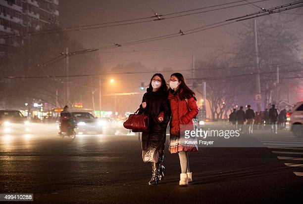 Chinese women wear masks as protection from the pollution as they cross a road on December 1, 2015 in Beijing, China. China's capital and many cities...