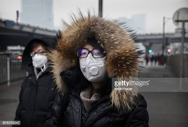 Chinese women wear masks as they walk in the street on a polluted day on December 12 2016 in Beijing China As a result of industry the use of coal...
