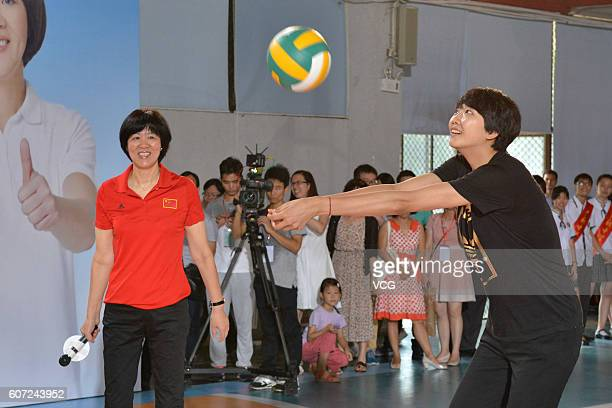 Chinese women's volleyball head coach Lang Ping guides while player Yuan Xinyue demonstrating volleyball during their visit Guangya High School on...