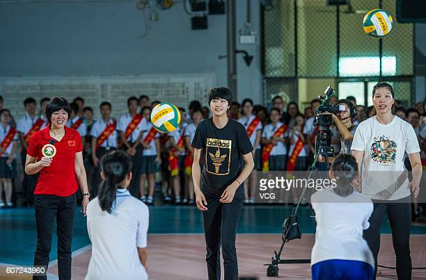 Chinese women's volleyball head coach Lang Ping guides while players Yuan Xinyue and Xu Yunli interacting with students during their visit Guangya...
