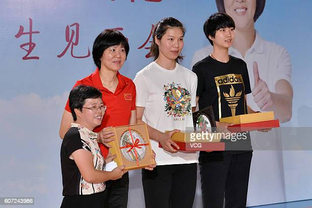 Chinese women's volleyball head coach Lang Ping players Xu Yunli and Yuan Xinyue pose on platform during their visit Guangya High School on September...