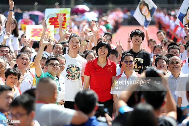 Chinese women's volleyball player Xu Yunli head coach Lang Ping and player Yuan Xinyue pose with teachers and stidents at Guangya High School on...