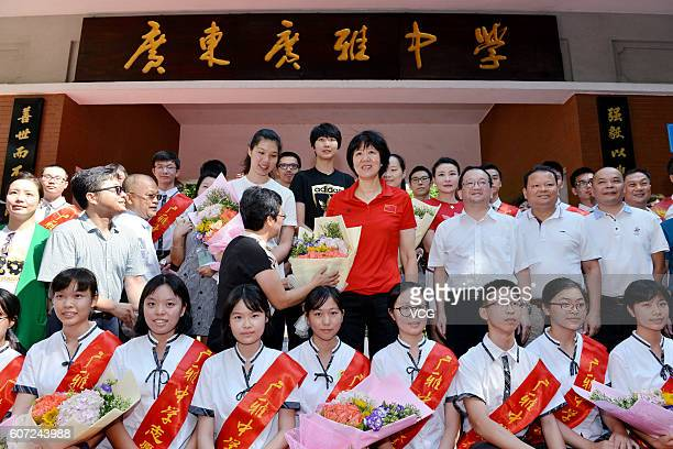 Chinese women's volleyball players Xu Yunli Yuan Xinyue and their head coach Lang Ping pose with teachers and students at Guangya High School on...
