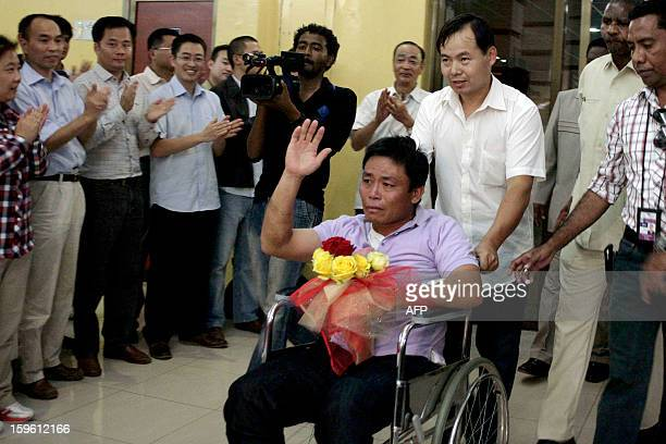 A Chinese worker abducted by Darfur rebels earlier this month waves on his wheelchair upon his arrival at the Khartoum airport after his release on...