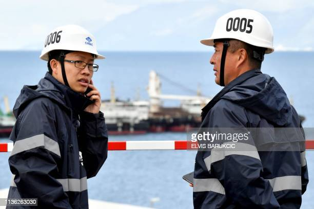 Chinese worker and engineer speaks on the phone next to one of his colleague, on April 11 in Peljesac, in the construction site of the bridge...