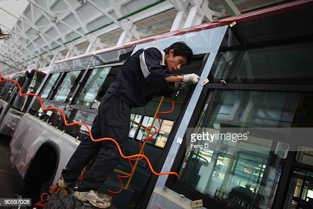 Chinese worker assembles a hybrid bus at a factory of Chinese auto manufacturer Beiqi Foton Motor Co Ltd on September 11 2009 in Beijing China A...
