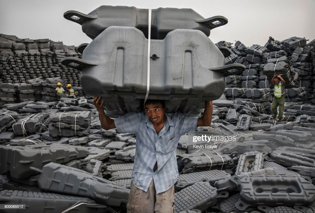 A Chinese worker carries flotation devices used to support panels to be used in a large floating solar farm project under construction by the Sungrow Power Supply Company on a lake caused by a collapsed and flooded coal mine on June 12, 2017 in Huainan, Anhui province, China. The floating solar field, billed as the largest in the world, is built on a part of the collapsed Panji No.1 coal mine that flooded over a decade ago due to over-mining, a common occurence in deep-well mining in China's coal heartland. When finished, the solar farm will be made up of more than 166,000 solar panels which convert sunlight to energy, and the site could potentially produce enough energy to power a city in Anhui province, regarded as one of the country's coal centers. Local officials say they are planning more projects like it, marking a significant shift in an area where long-term intensive coal mining has led to large areas of subsidence and environmental degradation. However, the energy transition has its challenges, primarily competitive pressure from the deeply-established coal industry that has at times led to delays in connecting solar projects to the state grid. China's government says it will spend over US $360 billion on clean energy projects by 2020 to help shift the country away from a dependence on fossil fuels, and earlier this year, Beijing canceled plans to build more than 100 coal-fired plants in a bid to ease overcapacity and limit carbon emissions. Already, China is the leading producer of solar energy, but it also remains the planet's top emitter of greenhouse gases and accounts for about half of the world's total coal consumption.