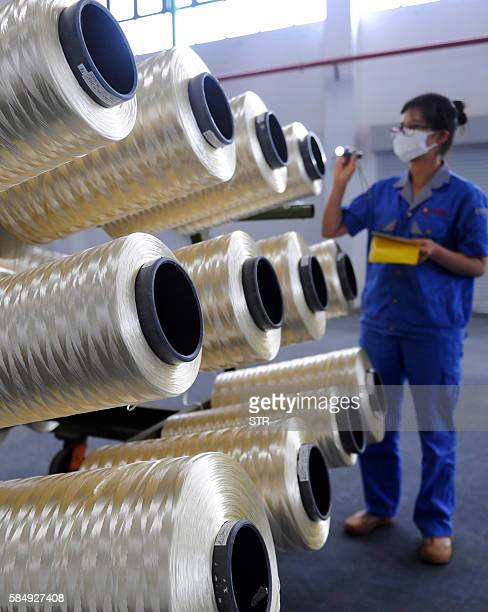 A Chinese worker checks carbon fiber silk thread at a carbon fiber factory in Lianyungang in eastern China's Jiangsu province on August 1 2016...