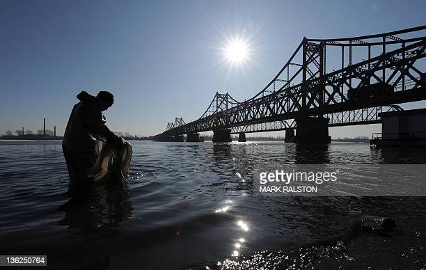 Chinese worker cleans up trash from the Yalu River and beside the Yalu Bridge which leads into North Korea one day after the memorial service for the...
