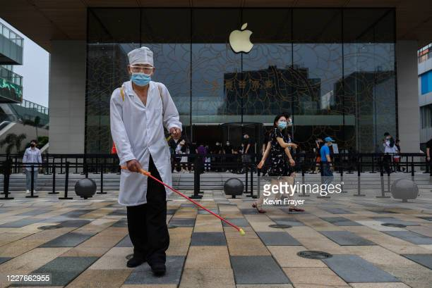Chinese worker disinfects the area at the official opening of the new Apple Store in the Sanlitun shopping area on July 17 2020 in Beijing China The...